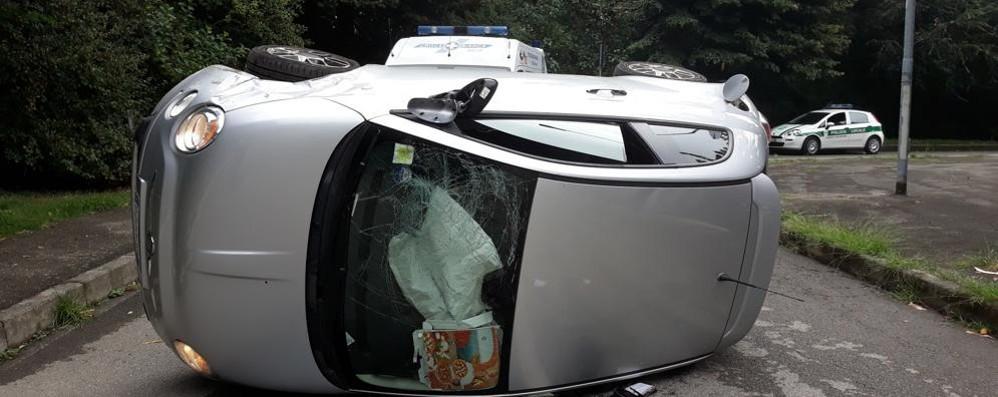 Finiscono contro un'auto in sosta e si ribaltano in città a Melegnano - VIDEO