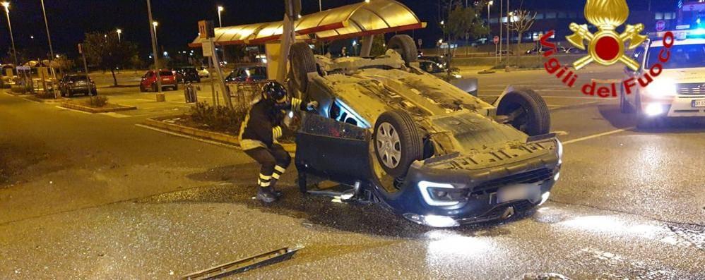 Scontro nel parcheggio del supermercato: auto ribaltata e un ferito